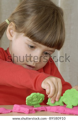 Little girl playing with a clay
