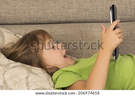 Little girl playing with a digital tablet at home on a sofa  - stock photo