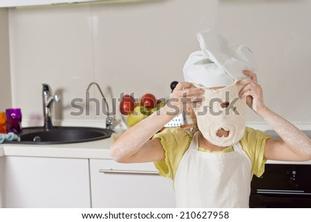 Little girl playing with a dough mask holding up a freshly rolled out portion of pastry through which she has punched a mouth and nose - stock photo