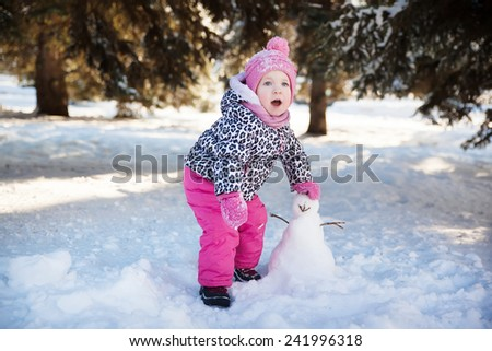little girl playing with a snowman - stock photo