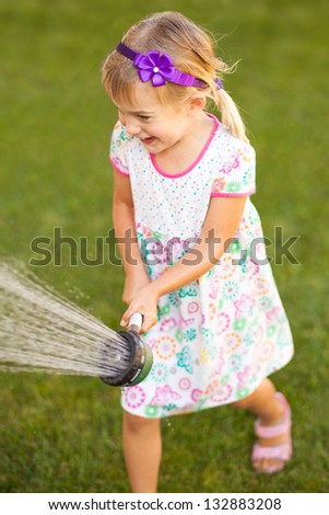 Little girl playing with a water sprayer - stock photo