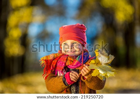 Little girl playing with autumn leaves in the park - stock photo
