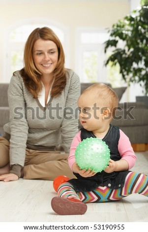 Little girl playing with ball sitting on living room floor, mum in background looking happy.