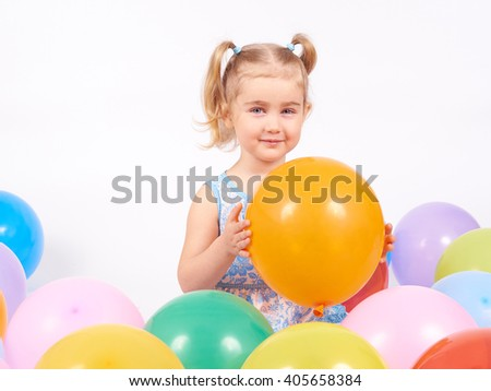Little girl playing with balloons.Happy little girl holding balloon.Smiling kid. Isolated on white background.