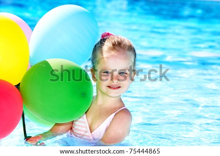 little girl playing with balloons in swimming pool. - stock photo