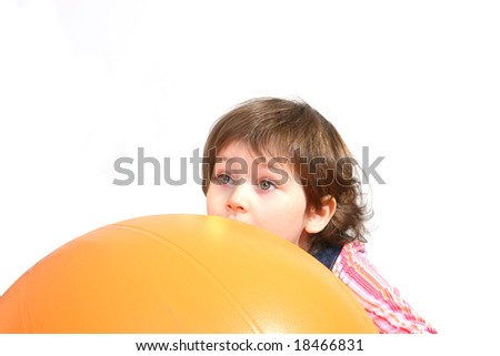 Little girl playing with big orange ball on white ground