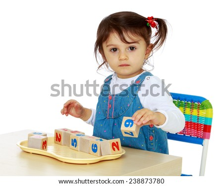 Little girl playing with blocks sitting at the table. Isolated on white background studio photo. - stock photo