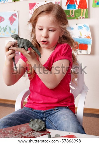 Little girl playing with clay. - stock photo