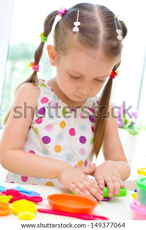 Little Girl Playing with Color Play Dough - stock photo
