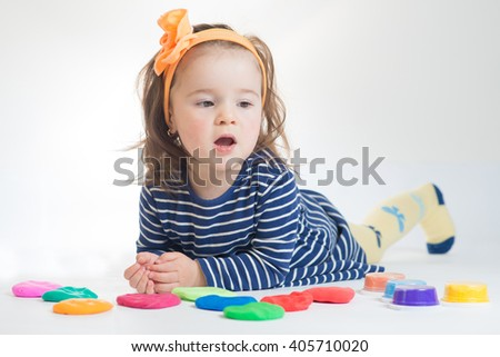 Little girl playing with colored plasticine isolated on the white background