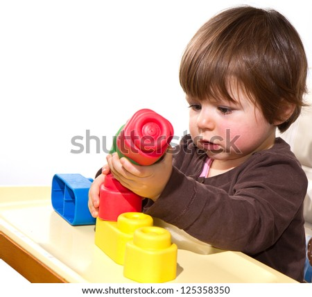 little girl playing with colorful blocks - stock photo