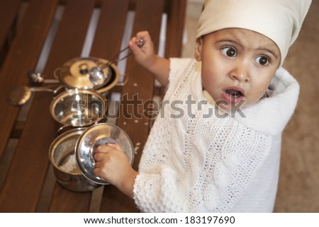 little girl playing with cooking utensils. looking up with his mouth open, surprised expression - stock photo