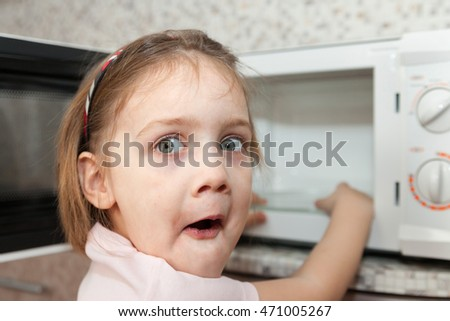 Little girl playing with dangerous kitchen appliance