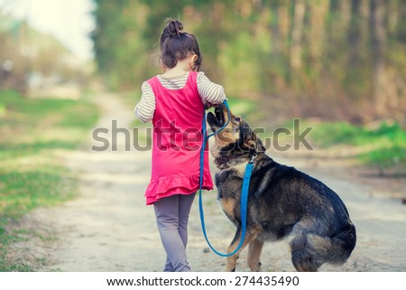 Little girl playing with dog in the village back to camera - stock photo
