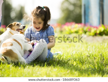 Little girl playing with dogs