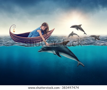 Little girl playing with dolphin - stock photo