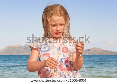 Little girl playing with dry grass on the seashore against the sea landscape background
