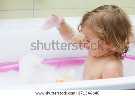 Little girl playing with foam in the bath. - stock photo