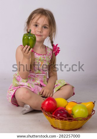 little girl playing with fruit and vegetables