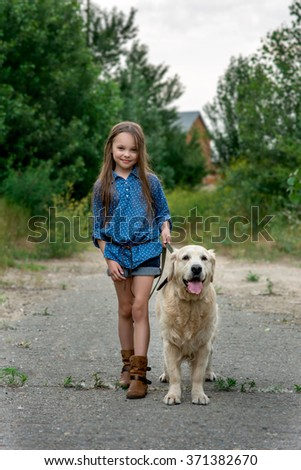 Little girl playing with her big dog outdoors in rural areas in summer. kid with  golden retriever in the summer park. Looking into the camera.