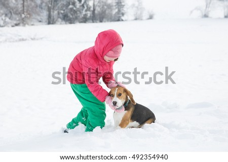 Little girl playing with her dog in a snowy landscape, having winter fun. Active family lifestyle, outdoor and natural childhood, fun and carefree childhood concept.