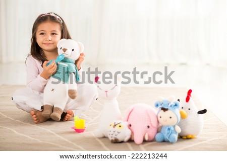 Little girl playing with her knitted toys - stock photo