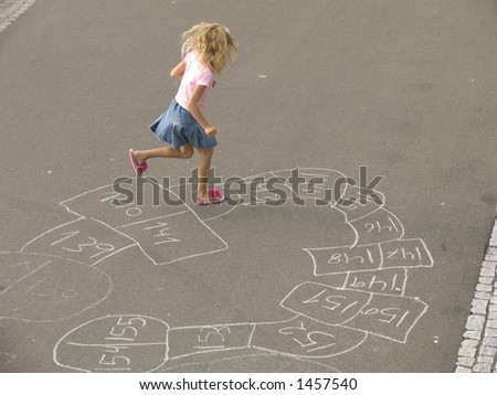 Little girl playing with her selfdesigned hopscotch. - stock photo