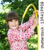 Little girl playing with hose and water - stock photo