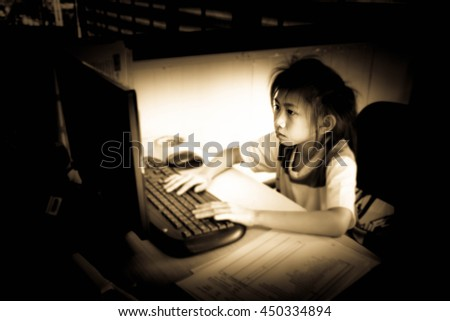 Little girl playing with laptop,Asian little girl,Blurry portrait,Vintage sepia tone - stock photo