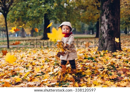 Little girl playing with leaves