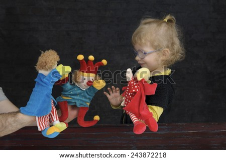 little girl playing with marionettes - stock photo