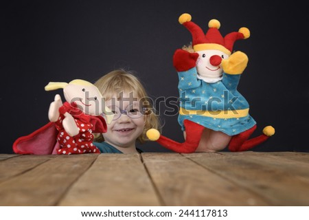 little girl playing with marionettes