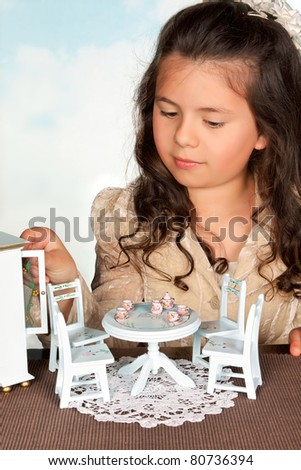 Little girl playing with miniature furniture and tea service - stock photo