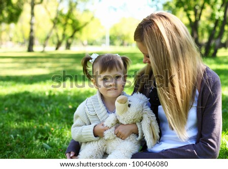 Little girl playing with mother in green summer park