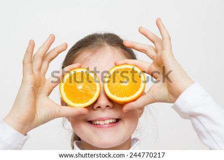 Little girl playing with orange fruits