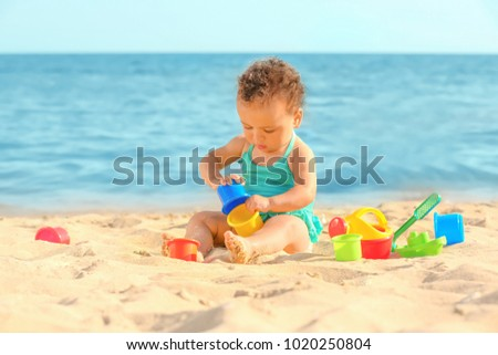 Little girl playing with sand toys on beach