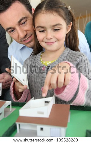 Little girl playing with scale model of housing - stock photo