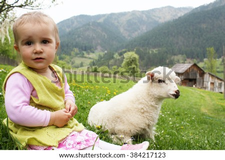 Little girl playing with sheep