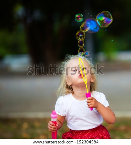 Little girl playing with spoon bubbles - stock photo