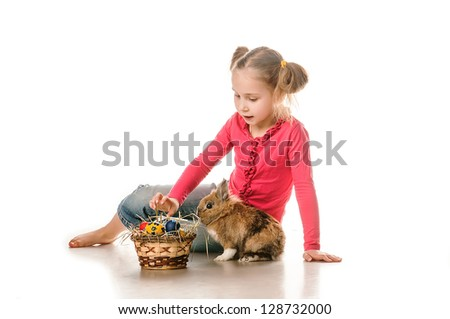 little girl playing with the Easter Bunny, decorated eggs are in the basket