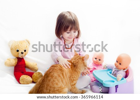 Little girl playing with toys and feeding a cat