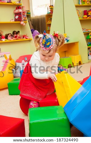 Little girl playing with toys in the playroom - stock photo