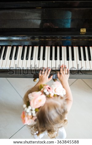 little girl plays a tune on the piano keys. Piano school for little girl - stock photo