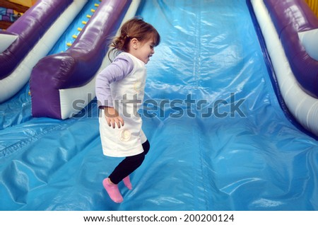 Little girl plays and jumps on Inflatable giant slide. - stock photo