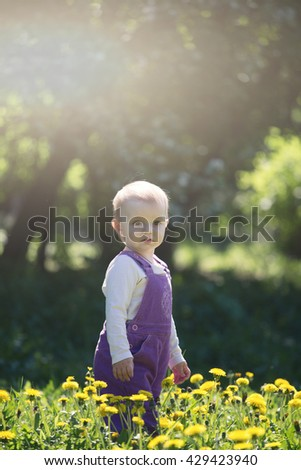 little girl plays on a glade with the blossoming dandelions - stock photo