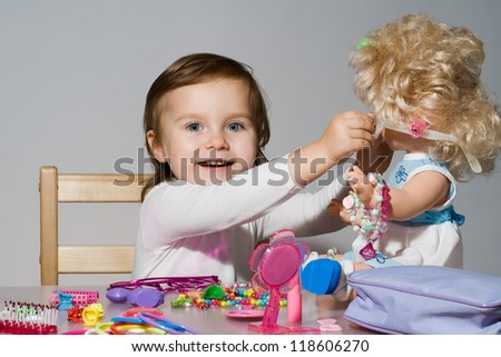 Little girl plays with a doll - stock photo
