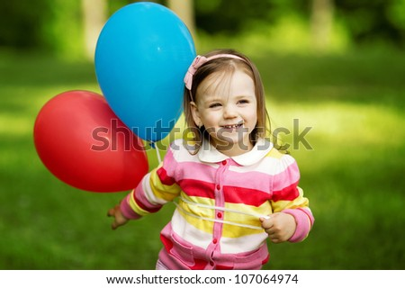 little girl plays with balloons - stock photo