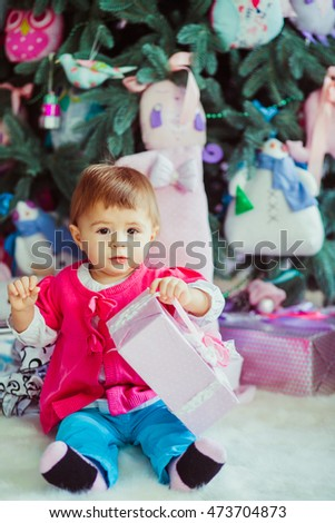 Little girl plays with pastel pink boes sitting under Christmas tree