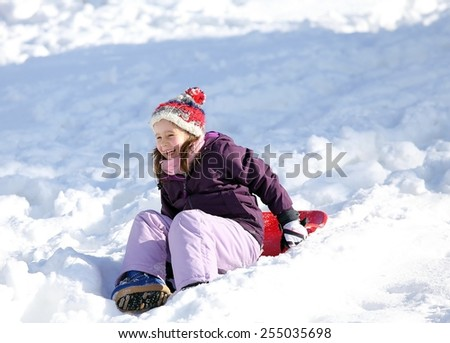 little girl plays with sledding on snow in the winter in the mountains - stock photo