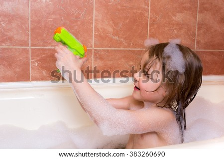little girl plays with water pistol in a bath with foam - stock photo